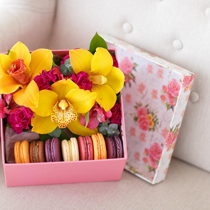 Букет из: альстромерия (розовый) — 1 шт., пиафлор — 1 шт., коробка (прямоугольник, средний) — 1 шт., рускус — 1 шт., эвкалипт — 1 шт., гвоздика кустовая (ярко-сиреневый) — 2 шт., орхидея цимбидиум 1 бутон (желтый) — 3 шт., макаронс 1 шт. — 7 шт. - Коробка с пирожными Macaron и тремя орхидеями цимбидиум