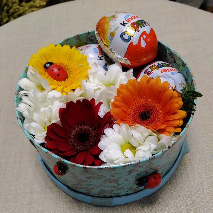 Яйцо киндер — 3 шт., Коробка (круг, малый) — 1 шт., Оазис — 1 шт., Лента — 1 шт., Гербера микс (микс (разных цветов)) — 3 шт., Хризантема Сантини (белый) — 3 ш…